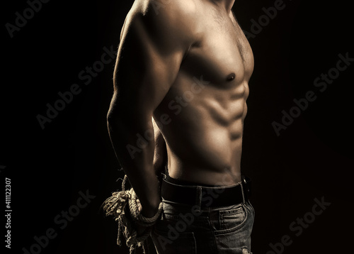 Fotografia Sexy man with muscular body with tied hands by rope.