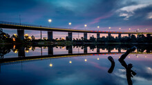 The Reflections Of The Melbourne City Skyline At Dusk In The Still Water Of The West Gate Bridge