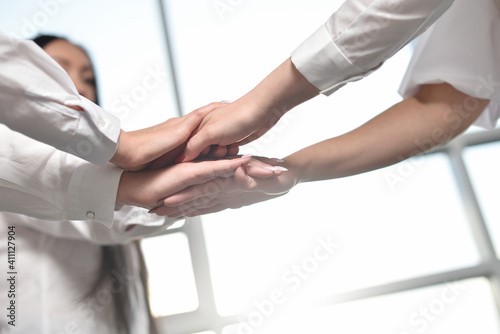 The united hands of female employees for concentration and teamwork success Fototapeta