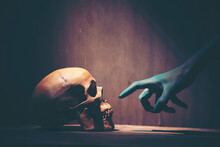 Cropped Painted Hand Of Person Pointing At Human Skull On Table In Dark