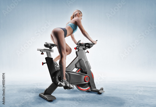 Obraz Beautiful slender and long-legged girl sits on an exercise bike. Side view. The concept of sports, bodybuilding, fitness, aerobics. healthy lifestyle. - fototapety do salonu