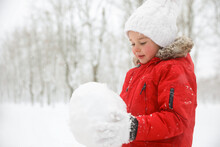 Cute Little Girl Holding Snowball Outdoors On Winter Day, Space For Text
