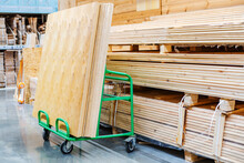 Large Sheets Of Plywood Lie On A Transport Cart In A Building Supplies Store. Copy Space