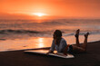 Leinwandbild Motiv Beautifull woman on tropical beach holding surfboard at sunset in Bali