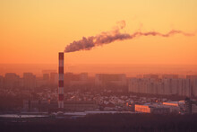 High Chimney With Smoke Above City Buildings At Sunset