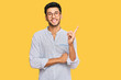 canvas print picture - Young handsome man wearing casual clothes and glasses with a big smile on face, pointing with hand and finger to the side looking at the camera.