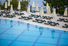 Plastic Sun Loungers And Parasols For Sun Protection Are Placed On The Tiles By The Pool In The Recreation Area