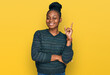 canvas print picture - Young african american woman wearing casual clothes with a big smile on face, pointing with hand and finger to the side looking at the camera.
