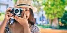 Young Latin Woman On Vacation Using Vintage Camera Walking At Street Of City.