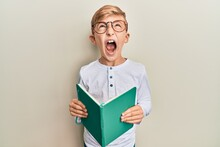 Little Caucasian Boy Kid Reading A Book Wearing Glasses Angry And Mad Screaming Frustrated And Furious, Shouting With Anger Looking Up.