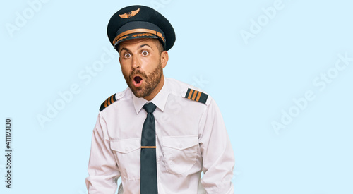 Handsome man with beard wearing airplane pilot uniform afraid and shocked with surprise expression, fear and excited face Fototapet