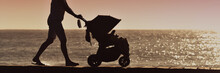 Silhouette Mother Pulling Baby Stroller Against Beach Sunset