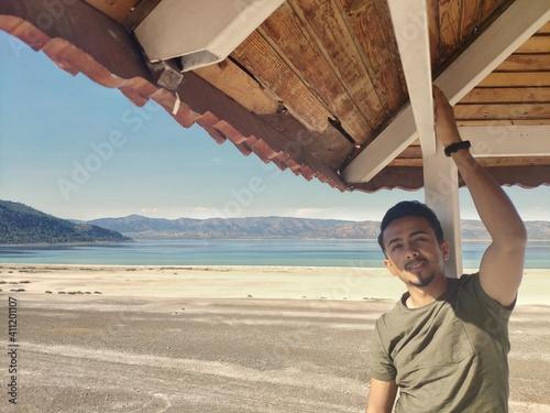 Fotografie, Obraz Portrait Of Man Touching Ceiling Of Gazebo At Beach