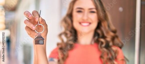 Obraz Young blonde girl smiling happy holding key of new house standing at the city. - fototapety do salonu