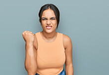Young Brunette Woman Wearing Casual Clothes Angry And Mad Raising Fist Frustrated And Furious While Shouting With Anger. Rage And Aggressive Concept.