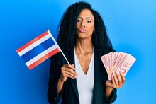 Middle Age African American Woman Holding Thailand Flag And Baht Banknotes Looking At The Camera Blowing A Kiss Being Lovely And Sexy. Love Expression.
