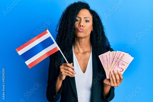 Fotografija Middle age african american woman holding thailand flag and baht banknotes looking at the camera blowing a kiss being lovely and sexy