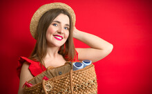 Happy Elegant Woman In Red Dress And Straw Hat   Straw Bag On  Red Background