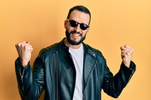 Young Man With Beard Wearing Black Leather Jacket And Sunglasses Screaming Proud, Celebrating Victory And Success Very Excited With Raised Arms