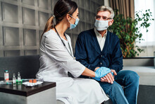 A Nurse In A Protective Mask And Gloves Holds The Hand Of An Older Man In A Protective Mask, Supporting And Helping The Elderly. Care For The Elderly. Doctor's Visit Home. Pandemic, Covid-19