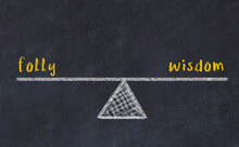 Concept Of Balance Between Folly And Wisdom. Chalk Scales And Words On It
