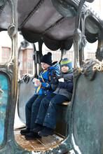 Children Sitting In Iron Carriage