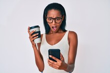 Young African American Woman Holding Takeaway Cup Of Coffee Using Smartphone Angry And Mad Screaming Frustrated And Furious, Shouting With Anger. Rage And Aggressive Concept.