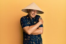 Middle Age Bald Man Wearing Traditional Asian Straw Hat Hugging Oneself Happy And Positive, Smiling Confident. Self Love And Self Care