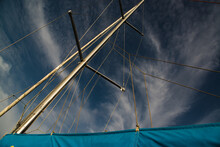 Blue Sail And Yacht Mast Against The Sky With Clouds