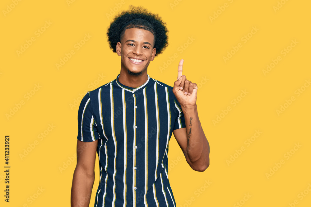 Fototapeta African american man with afro hair wearing casual clothes showing and pointing up with finger number one while smiling confident and happy.