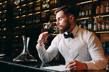 Young Handsome Man Sommelier Tasting Red Wine In Cellar.