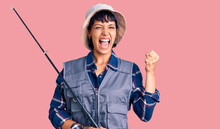 Young Brunette Woman With Short Hair Wearing Fisherman Equipment Screaming Proud, Celebrating Victory And Success Very Excited With Raised Arms