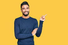 Young Man With Beard Wearing Casual Blue Winter Sweater Smiling Happy Pointing With Hand And Finger To The Side