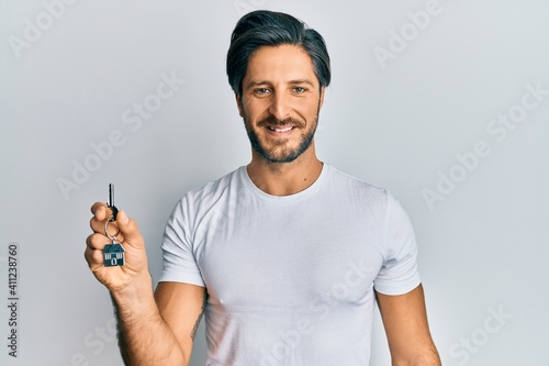 Fotografia, Obraz Young hispanic man holding keys of new home looking positive and happy standing