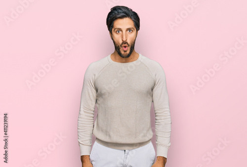 Obraz Young hispanic man wearing casual clothes scared and amazed with open mouth for surprise, disbelief face - fototapety do salonu