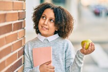 Adorable Hispanic Student Child Girl Smiling Happy Holding Green Apple At The City.