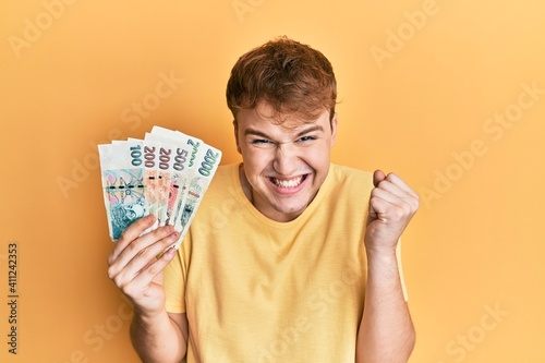 Young caucasian man wearing glasses holding czech koruna banknotes screaming proud, celebrating victory and success very excited with raised arm