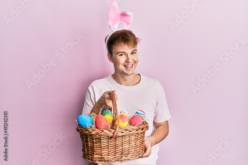 Young caucasian man wearing cute easter bunny ears holding wicker basket with colored eggs looking positive and happy standing and smiling with a confident smile showing teeth