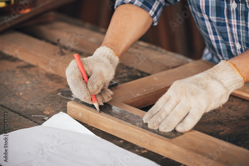 Fotografia closeup man carpenter measuring wood with ruler in workshop(vintage tone)