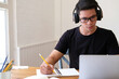 Young Man Wearing Headphones While Studying