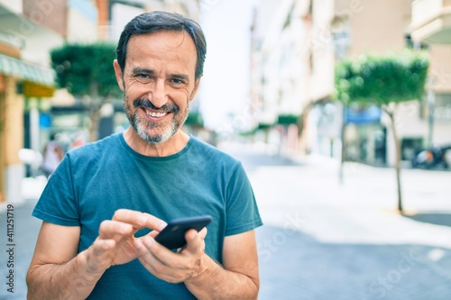 Obraz Middle age man with beard smiling happy outdoors using smartphone - fototapety do salonu