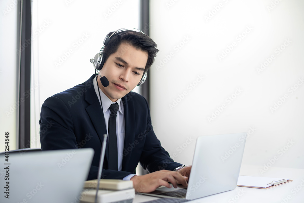 Fototapeta Asian man service Agent speak with a customer call center at the office.