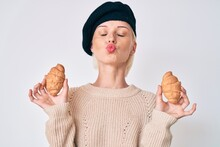 Young Caucasian Woman Wearing French Look With Beret Holding Croissants Looking At The Camera Blowing A Kiss Being Lovely And Sexy. Love Expression.