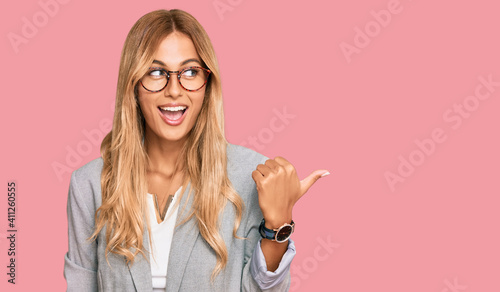 Fotografia Beautiful blonde young woman wearing business clothes smiling with happy face looking and pointing to the side with thumb up