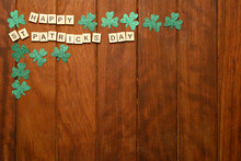 Wooden Letters Making The Phrase Happy Saint Patricks Day And Green Clovers On A Wood Background, Top View Place For Text