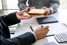 Midsection Of Businessman Signing While Client Giving Bribe At Office