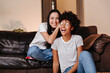 canvas print picture - Two young and beautiful girls with smiles on their faces are resting and having fun sitting on a big sofa