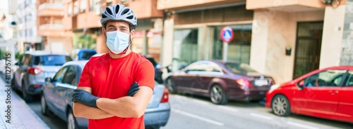 Obraz Young delivery man wearing bike helmet and coronavirus protection medical mask standing at town street. - fototapety do salonu