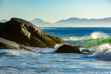 Waves Crashing Against The Rocks At Summer Dawn On Devil Beach In Ipanema Rio De Janeiro With Mountains At Background
