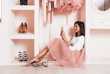 Young Beautiful Smiling Hipster Female In Trendy Summer Dress. Sexy Carefree Woman Sitting In Pink Wardrobe. Positive Model Having Fun. She Looking At Cellphone Screen And Using Apps, Purchase Clothes